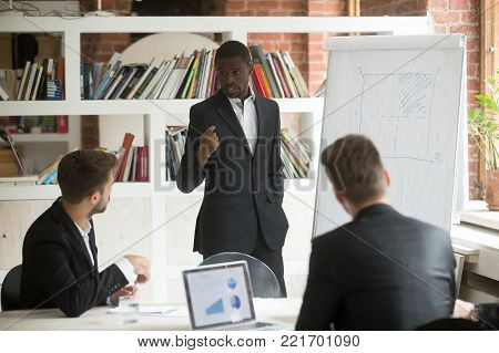 African american businessman giving presentation to partners working with flip chart at corporate meeting, black business coach explaining project strategy using whiteboard on group office training
