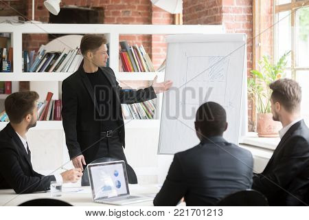 Confident businessman presenting project to diverse investors at office meeting, ceo giving flip chart presentation, planning project or developing new strategy, explaining idea to multiracial team