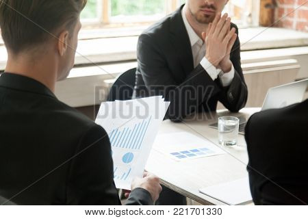 Businessman holding financial report with graphs charts at meeting with partners, executive team analyzing project statistics work result, investor considering startup investment, close up rear view