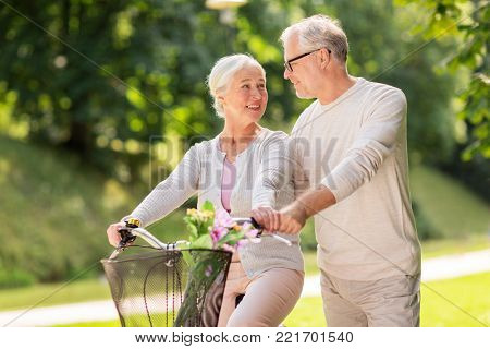 old age, people and lifestyle concept - happy senior couple with fixie bicycle talking at summer city park