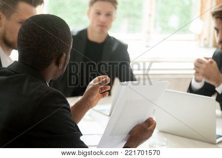African businessman holding documents talking to clients at meeting, black entrepreneur convincing partners to make deal, negotiation skills and influence in business concept, close up rear view