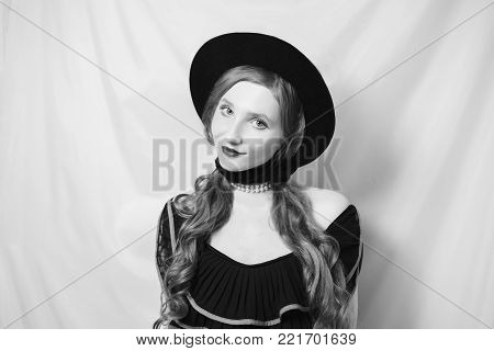 Retro girl in a black dress on a white background. Black and white art monochrome photography. Black and white creative photography. Black and white conceptual image. Beautiful black and white background. Black and white portrait.