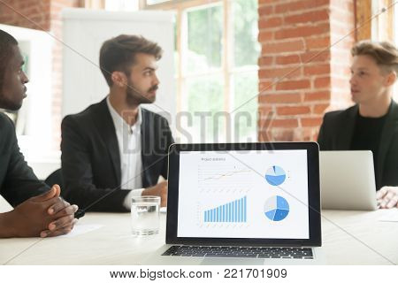 Project statistics on laptop screen with businessmen talk negotiate at background, executive team discussing project development work result, analyzing financial report charts graphs at meeting