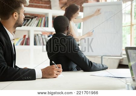 Diverse focused businessmen in suits listening to female coach giving presentation on flipchart sitting making notes at conference meeting table, corporate training business education seminar concept