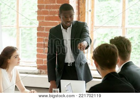 Rude impolite african businessman pointing finger at colleague on team meeting, angry black boss scolding white employee for bad work, multiracial conflict at workplace, obnoxious behavior in office