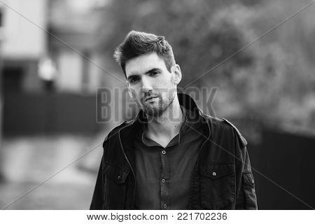 Young attractive cheerful man with dark hair. Black and white art monochrome photography. Black and white creative photography. Black and white conceptual image. Beautiful black and white background. Black and white portrait.