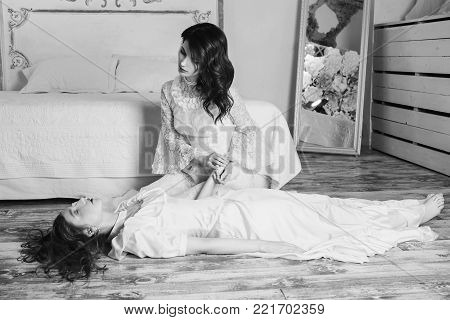 Black and white art monochrome photography. Black and white creative photography. Black and white conceptual image. Beautiful black and white background. Black and white portrait. Two beautiful girls with long hair in a beautiful white wedding Victorian d