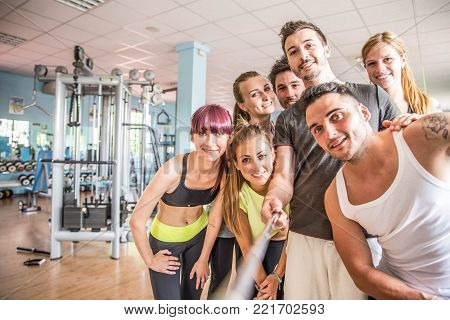 Group of sportive people in a gym taking selfie - Happy sporty friends in a weight room while training - Concepts about lifestyle and sport in a fitness club