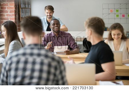 Smiling african-american businessman talking to colleague in coworking space, black attractive employee telling funny joke to coworker, friendly teamwork of co-working multiracial shared office
