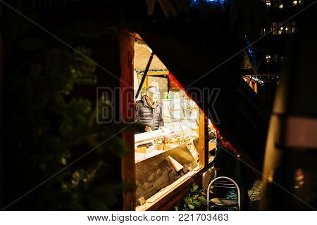 STRASBOURG, FRANCE - NOV 21, 2017: Silhouette of male vendor seen through the open chalet stall a day before the official inauguration of annual Christmas MArket in Strasbourg