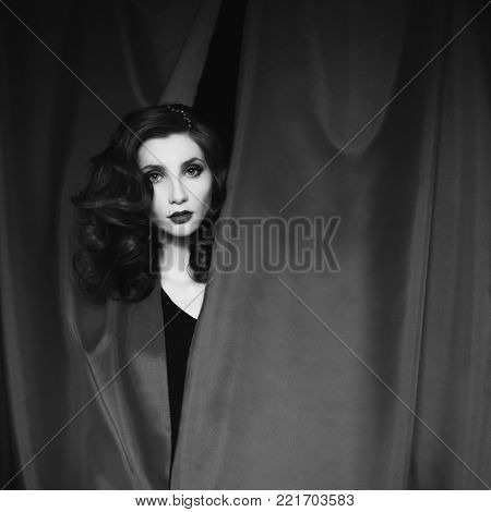 Black and white art monochrome photography. Black and white creative photography. Black and white conceptual image. Beautiful black and white background. Black and white portrait. A woman with curly hair in a black dress looking out of a gray fabric.