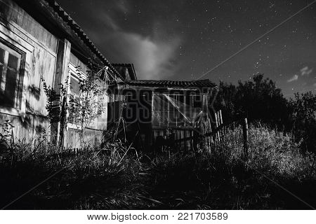 Old ramshackle house. The beautiful night scenery. Black and white art monochrome photography. Black and white creative photography. Black and white conceptual image. Beautiful black and white background.