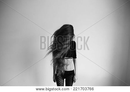 Girl with very long hair to the waist on a white background. Black and white art monochrome photography. Black and white creative photography. Black and white conceptual image. Beautiful black and white background. Black and white portrait.
