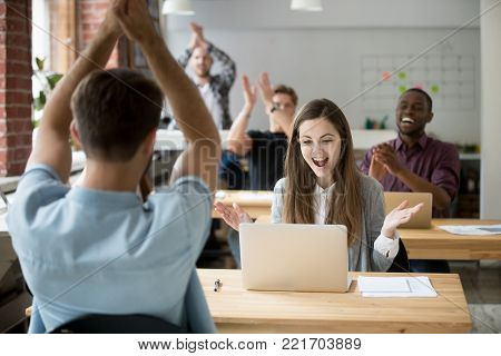 Excited woman looking at laptop screen surprised by good online news win achievement, corporate team colleagues congratulating coworker with business success clapping hands in coworking shared office