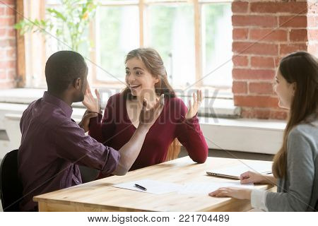 Multiracial couple excited by fantastic real estate investment best offer of buying dream house sale at meeting with mortgage broker, african american husband and caucasian wife happy to make deal