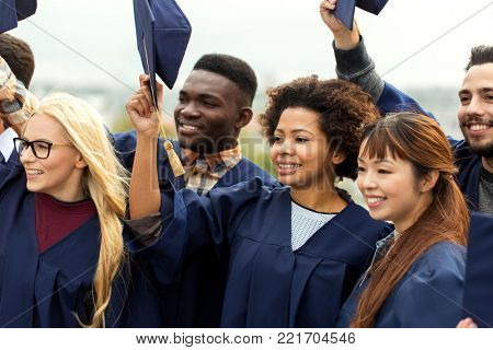 education, graduation and people concept - group of happy international students in bachelor gowns waving mortar boards