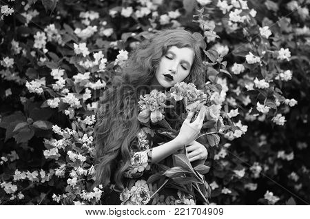 Black and white art monochrome photography. Black and white creative photography. Black and white conceptual image. Beautiful black and white background. Black and white portrait. Woman with pale skin and long hair in peony dress on background of a flower