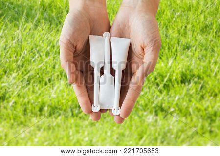 medicine, healthcare and pharmaceutics concept - hands holding tubes of micro enema over grass background
