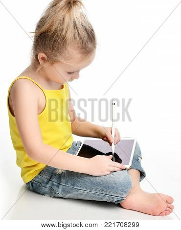 Young girl kid sitting reading learning drawing on digital tablet touch screen pad with pencil  in yellow shirt isolated on a white background