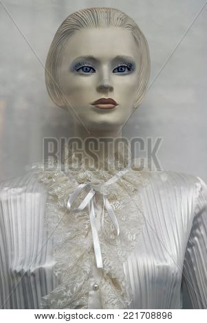 Mannequin white doll woman in white dress with sad look.