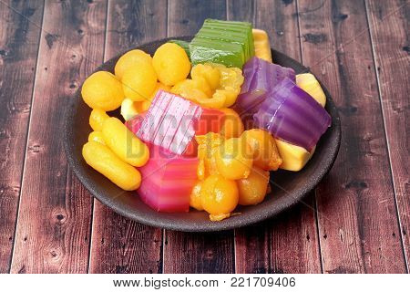 New year varity candy ,Colorful of Thai steamed layer cake in cube and fried pastry Golden Ball,Deep-fried candy drop and Jackfruit in old style of black plate.