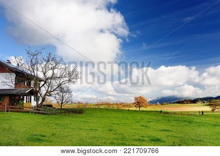 Scenic view of typical Bavarian lansdcape with cloudy blue sky on sunny autumn day. Wooden house with idyllic nature on background. Bavaria, Germany (Deutschland)