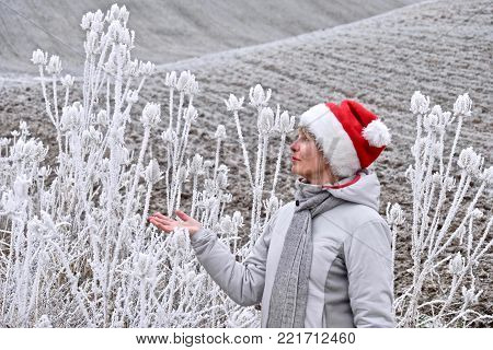 Middle age woman in winter landscape. Fields and farmlands covered with frost and snow. Christmas time in Palouse, southeast Washington. United States.