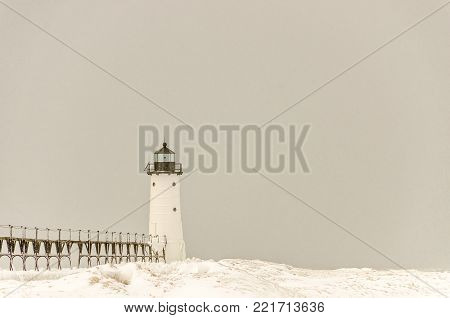 Snow is falling on the catwalk and light at Manistee, Michigan