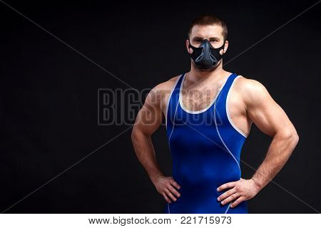 A young dark-haired man fighting Greco-Roman wrestling in a blue wrestling tights  and training mask  holding his hands at the waist against a black isolated background