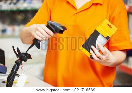 Seller with barcode scanner in shop