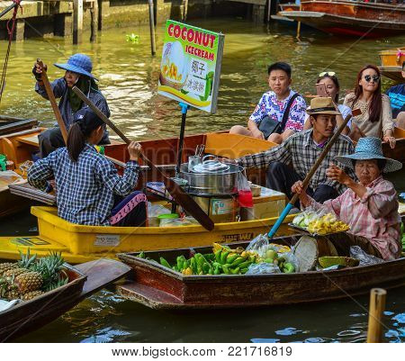 Bangkok, Thailand - Jun 19, 2017. Vendors selling food on wooden boat at Damnoen Saduak Floating Market in Bangkok, Thailand.