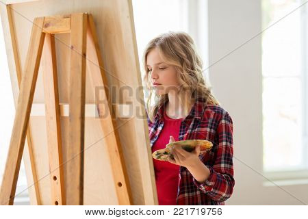 art school, creativity and people concept - student girl or artist with easel and palette painting at studio