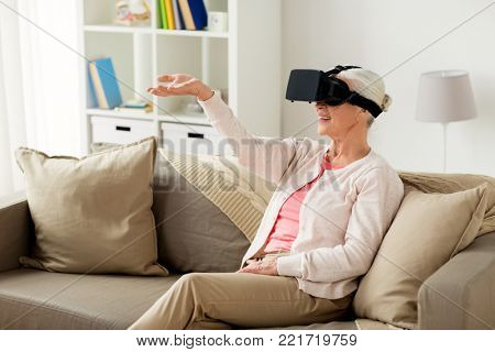 technology, augmented reality, entertainment and people concept - senior woman with virtual headset or 3d glasses playing videogame at home
