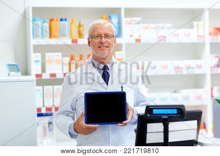 medicine, healthcare and people concept - senior apothecary at pharmacy cash register