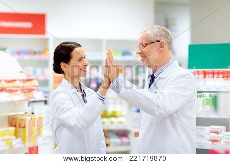 medicine, healthcare and technology concept - happy smiling apothecaries at pharmacy making high five