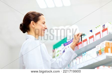 medicine, pharmaceutics, healthcare and people concept - happy female apothecary taking drug from shelf at pharmacy