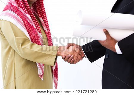 Arab business man shake hand with Asian business man in the blakc suit carrying a silver suit case.