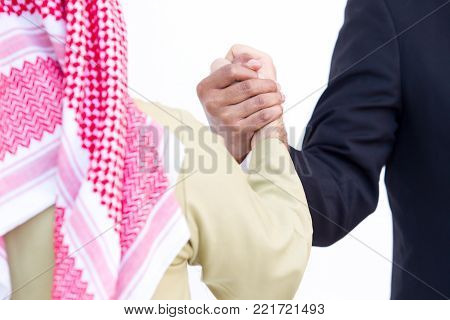 Shake hand between Arab and man in black suit close up on hand.