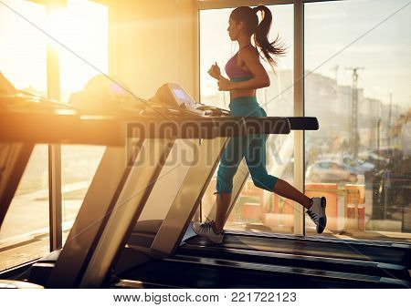 Young Healthy Athletic Woman Running On A Treadmill Near The Sunny Window In The Gym And Listening M