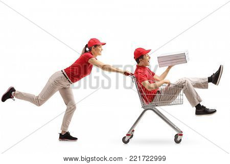 Teen pizza delivery boy with pizza boxes riding inside a shopping cart being pushed by a delivery girl isolated on white background