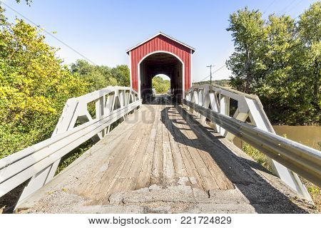 The red Wolf  Covered Bridge, with pony truss approaches, crosses the Spoon River in rural Knox County, Illinois.