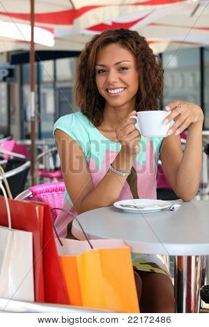 20 years old metis woman is drinking coffee on a terrace, she did shopping before