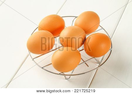 Raw Brown Chicken Eggs On An Iron Grate On A White Wooden Table. Ingredients For Cooking.