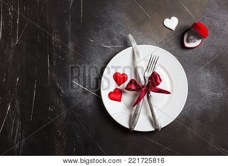 Valentines day table setting romantic dinner marry me wedding engagement ring in box with plate fork knife on dark background with copyspace. Love gift woman making proposal romantic holiday wedding