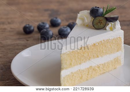 Blueberry cream cake on white plate on wood table in close up view. Vanilla sponge cake decorated with dairy whipped cream and fresh blueberry so soft sweet and delicious. Homemade bakery concept. Delicious blueberry cake ready to served.