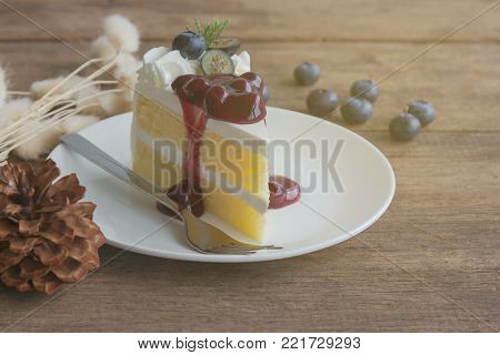 Blueberry Cream Cake On White Plate On Wood Table With Copy Space. Vanilla Sponge Cake Decorated Wit