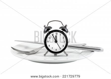 Alarm clock with fork and knife on the plate. Isolated on white. Time to eat.