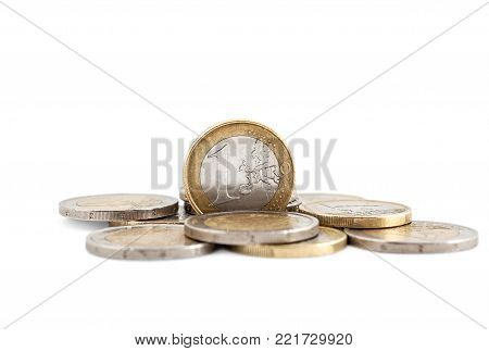One euro coin on heap of euro coins.