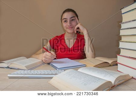 Student, Young Girl working on his homework. Portrait of pretty girl high school student studying and writing
