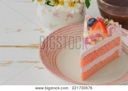 White chocolate strawberry yogurt cake decorated with fresh fruits and chocolate chunk. Sweet pink cake on white wood table with copy space. Delicious and sweet pink cake for Valentines or birthday party. Homemade bakery concept. Sweet strawberry cake.